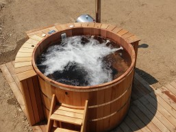 Red cedar hot tub stand alone on the deck with wood fired heater